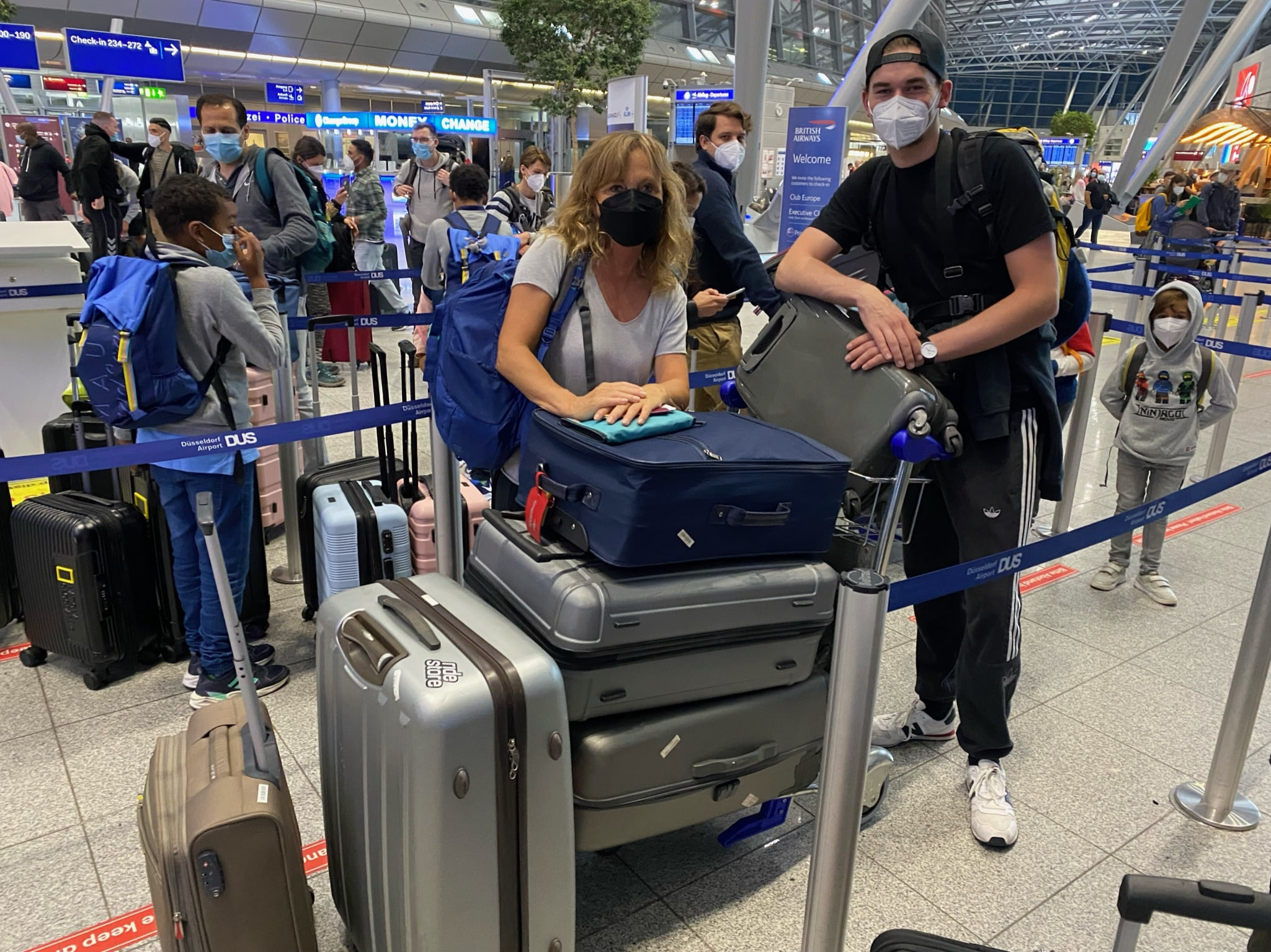 Zwei Menschen mit Masken stehen mit Koffern